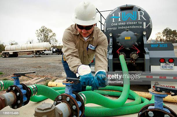 Anthony Schillings connects a pump to load water into his truck at a Heckmann Water Resources treatment plant that separates oil sediment and water...