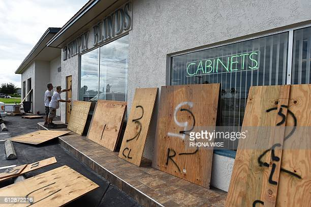 Anthony Schirado and Tom Kennedy put up plywood to cover the windows of store front ahead of Hurricane Matthew on Cocoa Beach Florida on October 5...