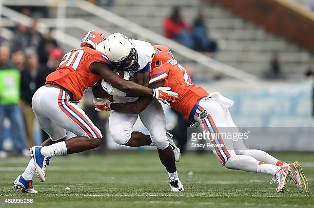 Anthony Scott of the East Carolina Pirates is brought down by Marcus Maye and Jabari Gorman of the Florida Gators during the fourth quarter of the...