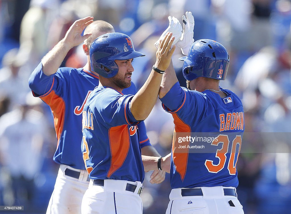 Anthony Seratelli #2 congratulates Andrew Brown #30 of the New York Mets after he scored the winning run in the bottom of the ninth inning on his single against the Detroit Tigers during a spring training game at Tradition Field on March 18, 2014 in Port St. Lucie, Florida. The Mets defeated the Tigers 5-4.
