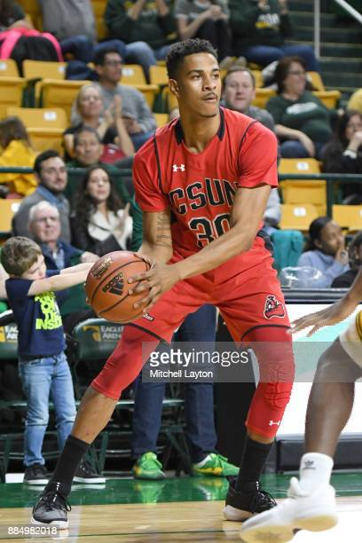Anthony Swan of the Cal State Northridge Matadors looks to pass the ball during a college basketball tournament against the George Mason Patriots at...