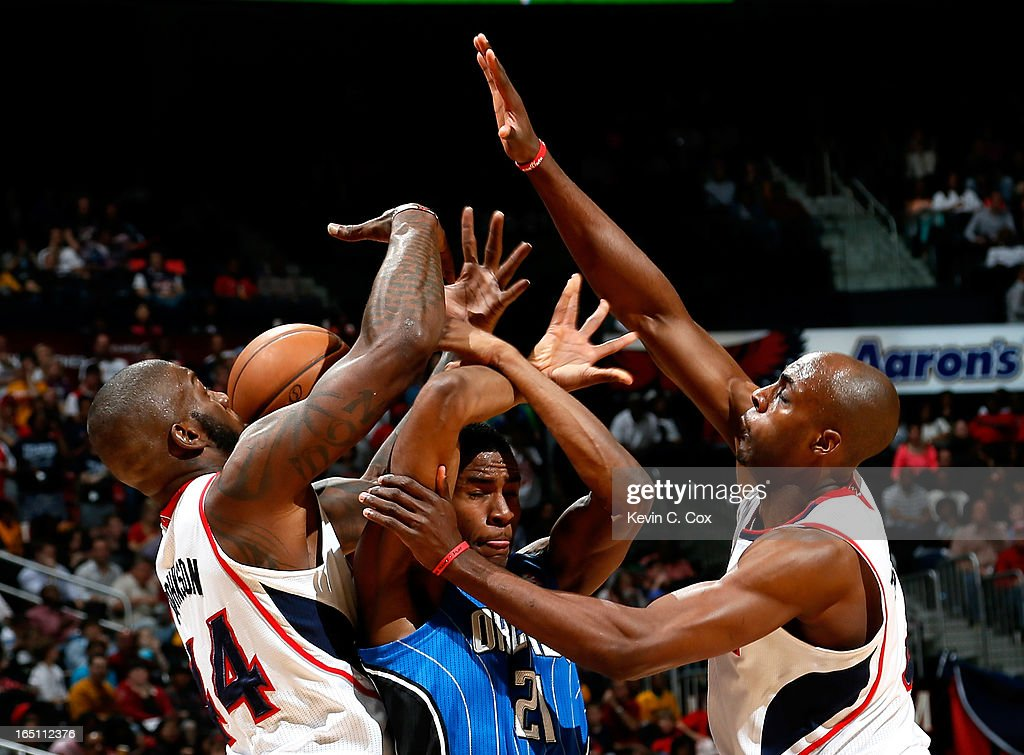 Anthony Tolliver #4 defends as Ivan Johnson #44 of the Atlanta Hawks strips the ball from Maurice Harkless #21 of the Orlando Magic at Philips Arena on March 30, 2013 in Atlanta, Georgia.