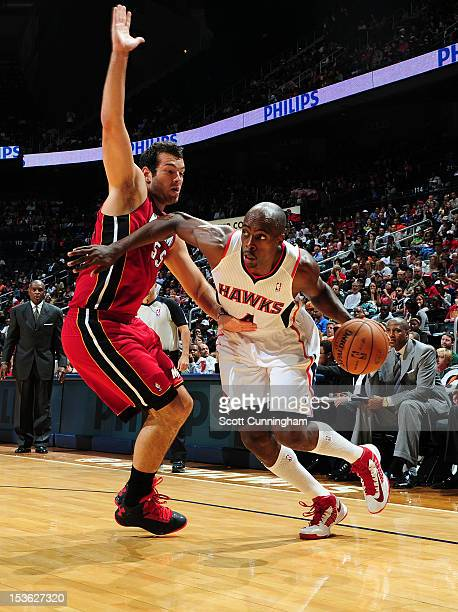 Anthony Tolliver of the Atlanta Hawks drives against Josh Harrellson of the Miami Heat at Philips Arena on October 7 2012 in Atlanta Georgia NOTE TO...