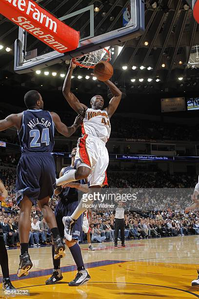 Anthony Tolliver of the Golden State Warriors dunks the ball against Paul Millsap of the Utah Jazz on April 13 2010 at Oracle Arena in Oakland...