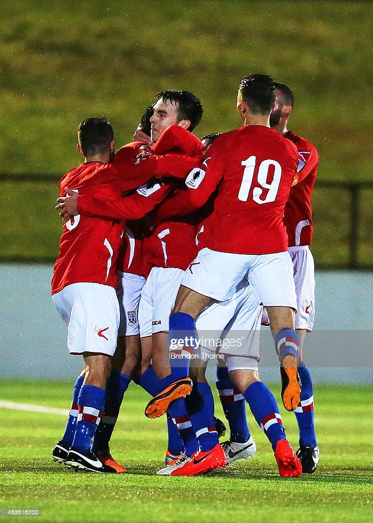 Anthony Tomelic of United celebrates with team mates after scoring the opening goal during the FFA Cup match between Sydney United 58 FC and the FNQ Heat at Sydney United Sports Centre on August 12, 2014 in Sydney, Australia.