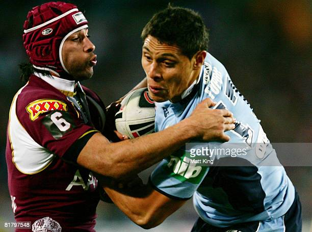 Anthony Tupou of the Blues is tackled by Jonathan Thrurston of the Maroons during match three of the ARL State of Origin series between the New South...
