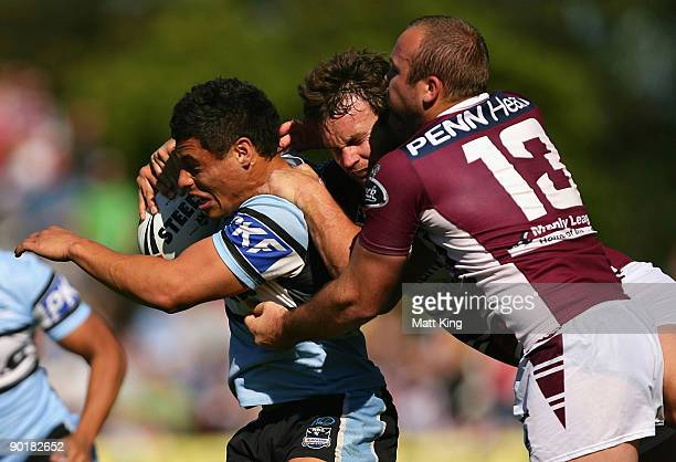 Anthony Tupou of the Sharks is tackled by Josh Perry and Glenn Stewart of the Sea Eagles during the round 25 NRL match between the ManlyWarringah Sea...