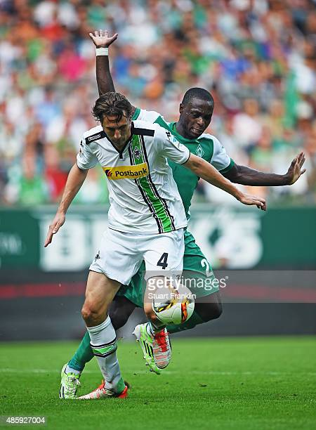 Anthony Ujah of Bremen is challenged by Roel Brouwers of Gladbach during the Bundesliga match between Werder Bremen and Borussia Moenchengladbach at...