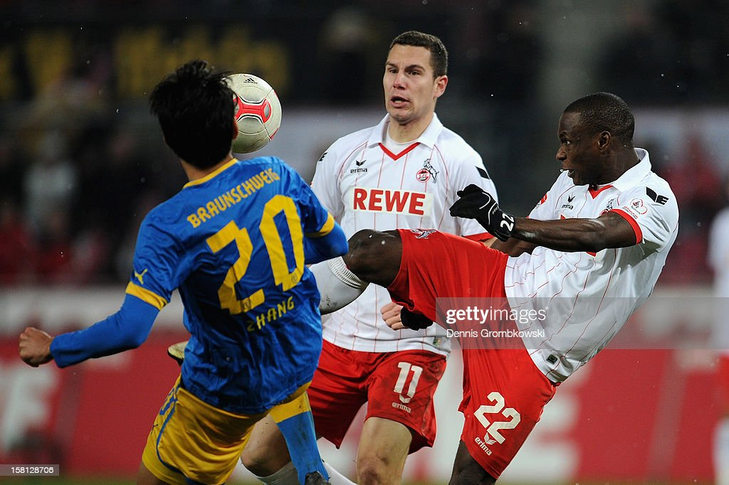 Anthony Ujah of Cologne controls the ball under the pressure of Chengdong Zhang of Braunschweig during the Bundesliga match between 1. FC Koeln and Eintracht Braunschweig at RheinEnergieStadion on December 10, 2012 in Cologne, Germany.