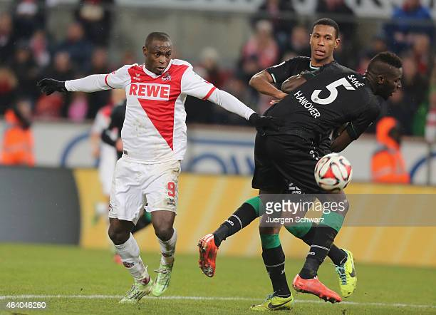 Anthony Ujah of Cologne tackles Salif Sane and Marcelo of Hannover during the Bundesliga match between 1 FC Koeln and Hannover 96 at...