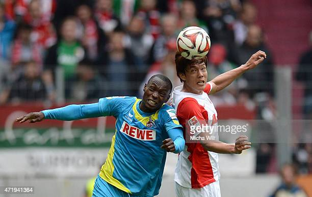 Anthony Ujah of Koeln and DongWon Ji of Augsburg jump for a header during the Bundesliga match between FC Augsburg and 1 FC Koeln at SGL Arena on May...