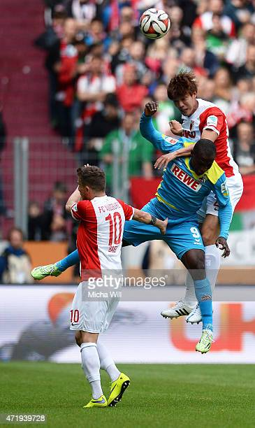 Anthony Ujah of Koeln and JeongHo Hong of Augsburg jump for a header during the Bundesliga match between FC Augsburg and 1 FC Koeln at SGL Arena on...