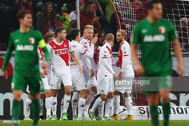 Anthony Ujah of Koeln celebrates his team's first goal with team mates during the Bundesliga match between 1 FC Koeln and FC Augsburg at...