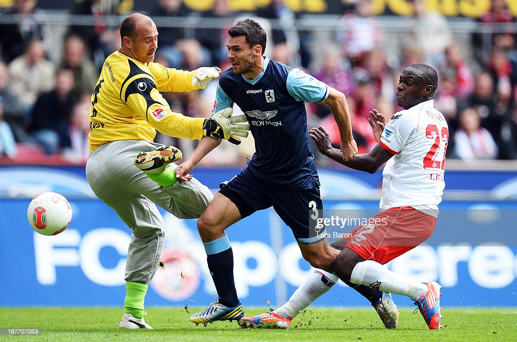 Anthony Ujah of Koeln is challenged by goalkeeper Gabor Kiraly and Grzegorz Wojkowiak of Muenchen during the Second Bundesliga match between 1. FC Koeln and TSV 1860 Muenchen at RheinEnergieStadion on April 28, 2013 in Cologne, Germany.