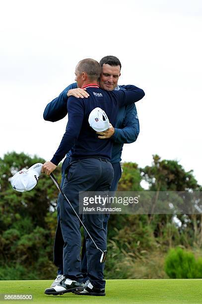 Anthony Wall of England is congratulated by Alex Noren of Sweden after he won their match on hole 18 on day four of the Aberdeen Asset Management...