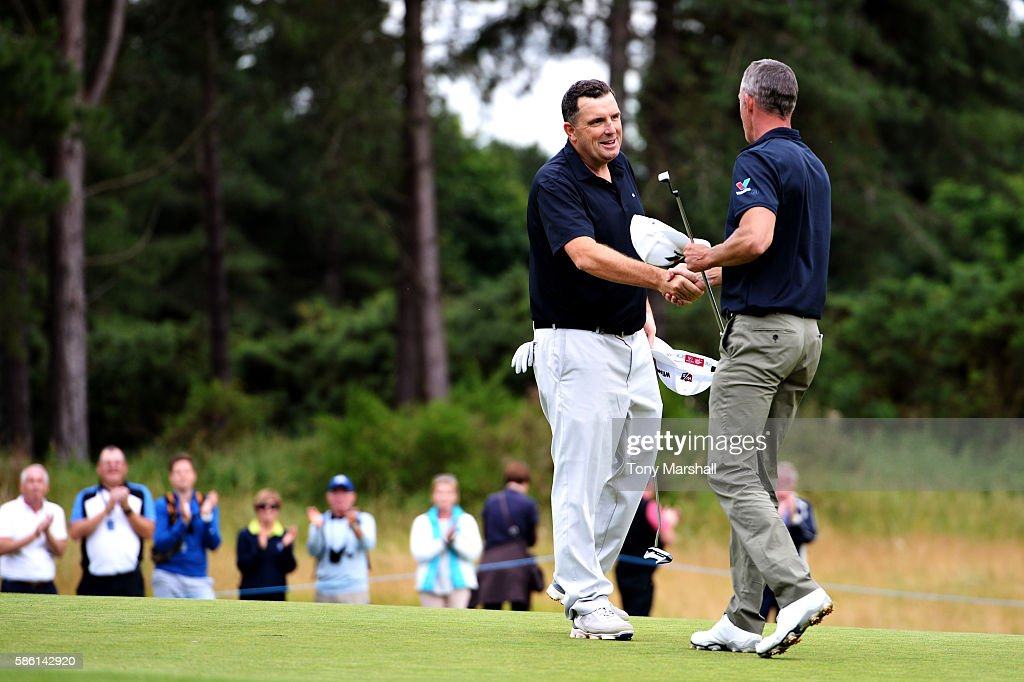 Anthony Wall of England shakes hands with Richard Green of Australia after winning their match on the first playoff hole on day two of the Aberdeen...