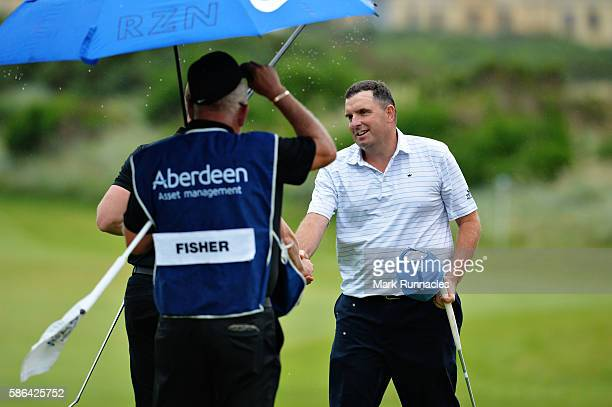 Anthony Wall of England with Oliver Fisher of England on hole 18 after winning their match on the fourth playoff hole on day three of the Aberdeen...