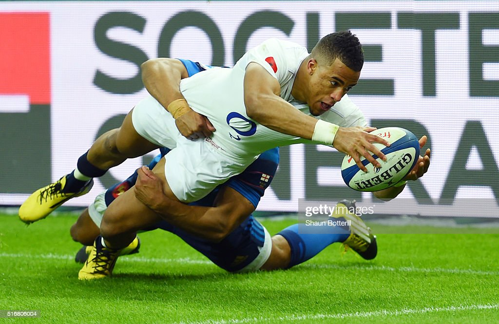 Anthony Watson of England scores his team's third try despite the tackled from Wesley Fofana of France during the RBS Six Nations match between France and England at the Stade de France on March 19, 2016 in Paris, France.