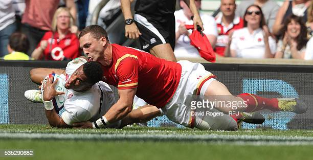 Anthony Watson of England stretches to score their second try despite being held by George North during the England v Wales International match at...