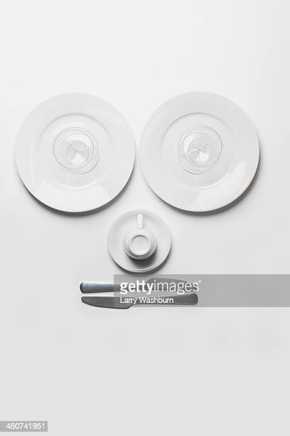 Anthropomorphic face made from plates, glasses, cup and knives