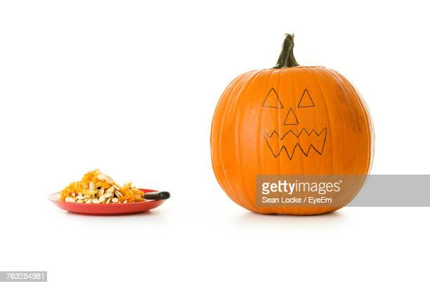 Anthropomorphic Face On Pumpkin By Seeds In Plate Against White Background