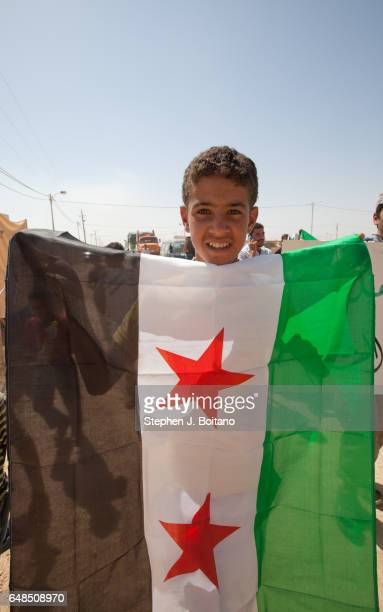 Anti Assad protesters march in the streets at the Zaatari Refugee Camp in Jordan The old style Syrian flags are being used Signs read 'Thanks JHCO...