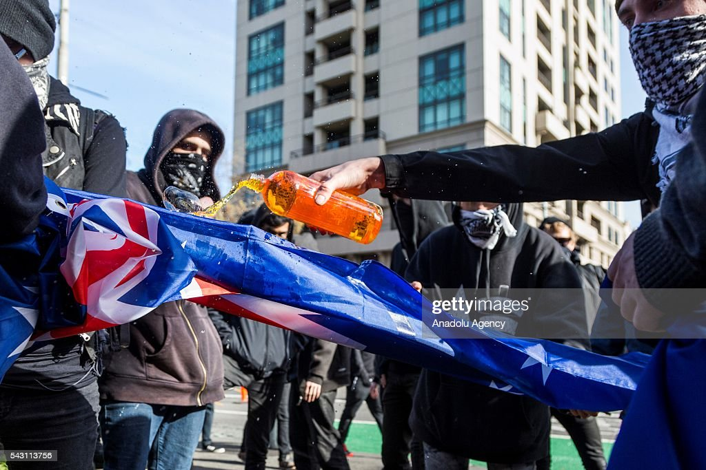 Anti fascists pour flammable liquid on the Australian Flag before burning it during a protest organized by the anti-Islam True Blue Crew supported by the United Patriots Front in Melbourne, Australia on June 26, 2016.