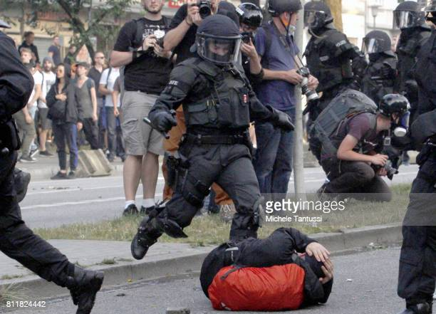 Anti G20 Summit protester lies on the ground as riot policemen charge during clashes with riot police on July 7 2017 in Hamburg Germany