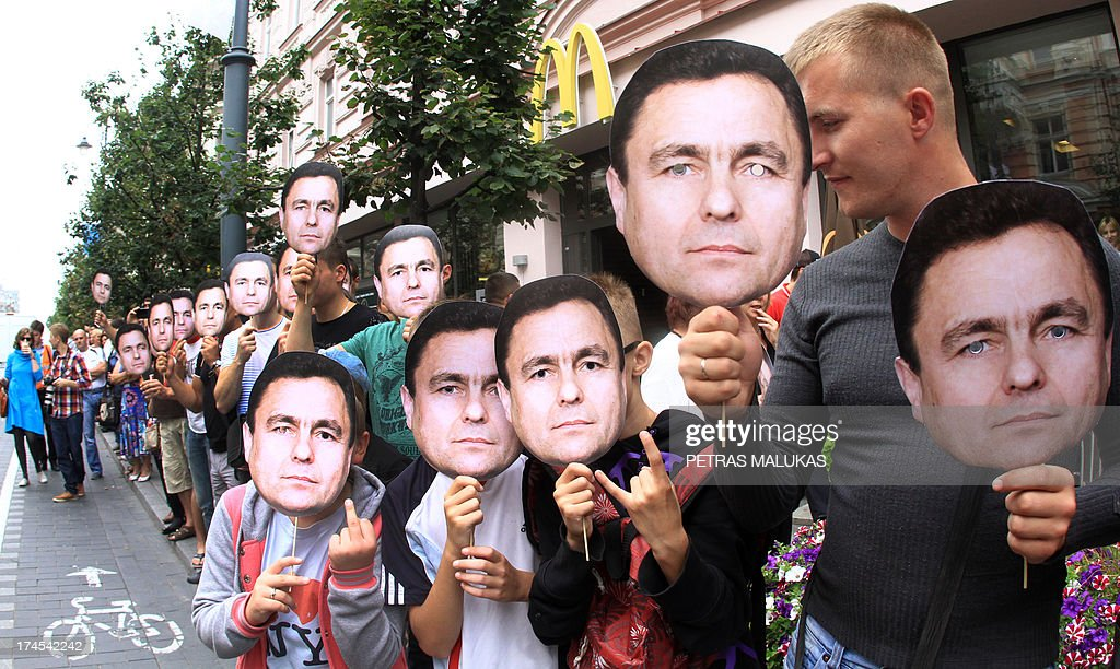 Anti Gay activists hold masks with a photo of Lithuanian politician from the Order and Justice party Petras Grazulis during the ''Baltic Pride 2013'' march on July 27, 2013, in Vilnius. Grazulis launched a bill that bans the dissemination of information to young people seen as promoting homosexuality. AFP PHOTO / PETRAS MALUKAS