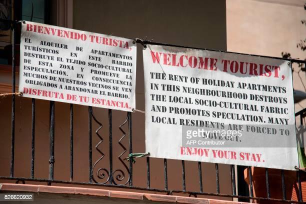 Anti gentrification banners adrresing tourists hang on a balcony at the Barceloneta neighborhood on August 5 2017 in Barcelona / AFP PHOTO / Josep...