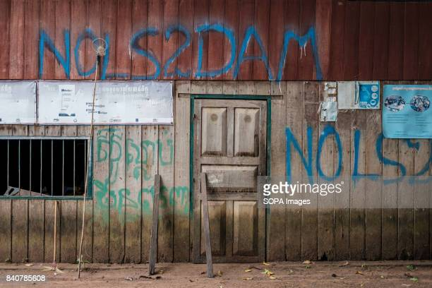 Anti LS2 dam graffiti are seen on the wall of a long house in Kbal Romeas village Local communities refuse to be removed Once the dam is in operation...