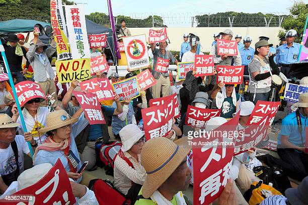 Anti nuclear demonstrators hold a sitin protest in front of the main gate as the Kyushu Electric Power Co activates the No 1 reactor of the Sendai...