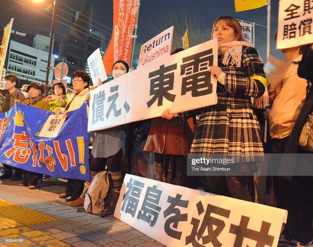 Anti nuclear protesters holding 'Compensate TEPCO, Return Fukushima' banners stand outside the Tokyo Electric Power Co headquarters on March 11, 2013 in Tokyo, Japan. Japan commemorates second anniversary of the Magnitude 9.0 earthquake and subsequent tsunami, that claimed more than 18,000 lives.