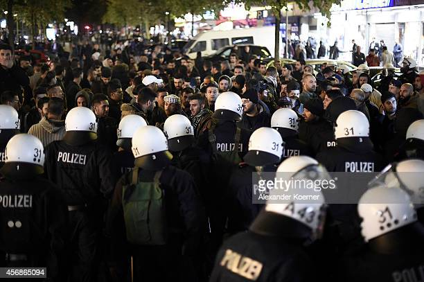 Anti riot police forces block the way of Kurdish protestors south of the Hamburg main train station during a rally against IS terror on October 8...