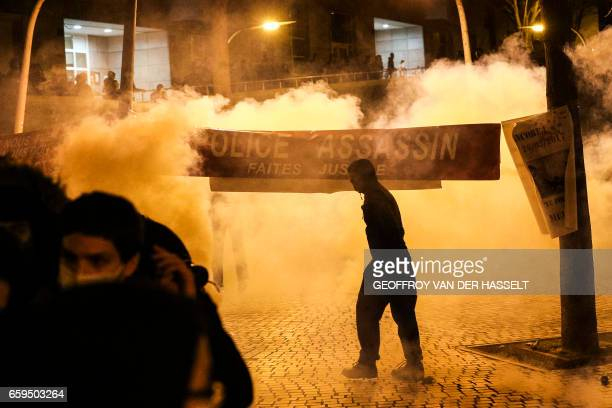 TOPSHOT Anti riot police throws tear gas as a man stand next to a banner reading 'Police murderer Do justice' during a protest in front of the police...