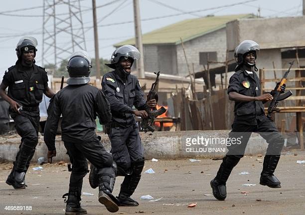 Anti riot policemen run during clash with Guinean opposition supporters on April 13 2015 in Conakry Several protesters were wounded on April 13 as...