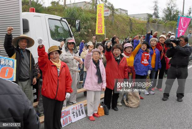 Anti US air base relocation protesters shout their slogan in front of the Camp Schwab on February 7 2017 in Nago Okinawa Japan Work to drop concrete...