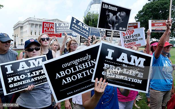 Antiabortion activists hold a rally opposing federal funding for Planned Parenthood in front of the US Capitol on July 28 2015 in Washington DC Sen...