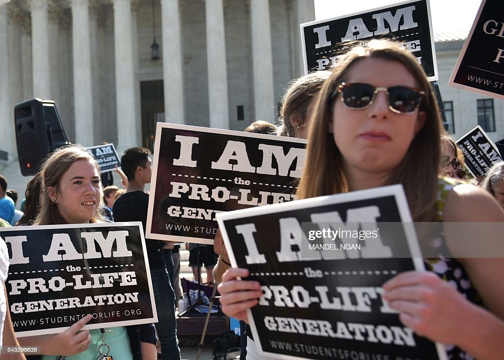 Anti-abortion activists hold placards before a US Supreme Court ruling on a Texas law placing restrictions on abortion clinics, outside of the Supreme Court on June 27, 2016 in Washington, DC. In a case with far-reaching implications for millions of women across the United States, the court ruled 5-3 to strike down measures which activists say have forced more than half of Texas's abortion clinics to close. / AFP / MANDEL
