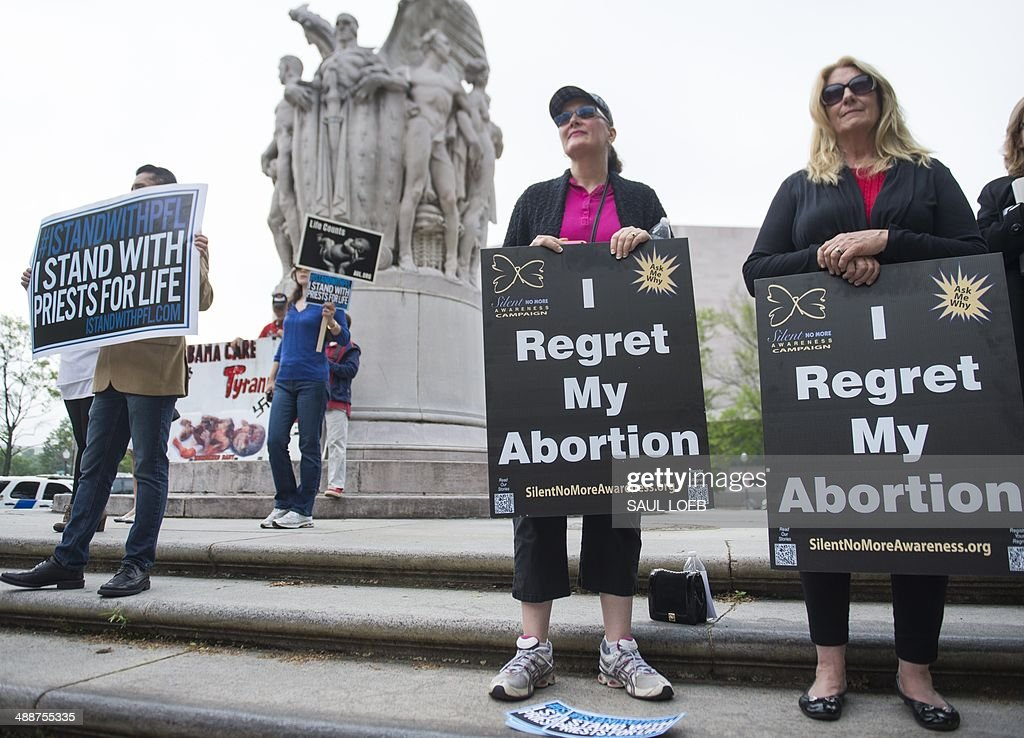 Anti-abortion demonstrators hold signs stating they regret their abortions during a Priests for Life protest outside the US Court of Appeals for the DC Circuit Court as the Court hears the oral arguments in the 'Priests for Life v. US Department of Health and Human Services (HHS)' case in Washington, DC, on May 8, 2014. The case centers around the HHS mandate in the Affordable Care Act, known as Obamacare, that religious organizations must cover contraceptions and abortion as part of their health insurance benefits, even if that goes against the organization's religious beliefs. AFP PHOTO / Saul LOEB