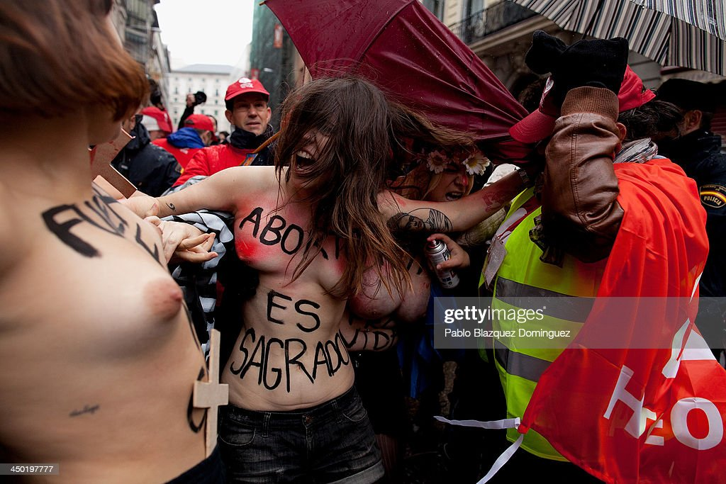 A anti-abortion protester sprays red paint at a FEMEN group activist with body painting reading 'abortion is sacred' as a Pro-Life demonstration takes place on Alcala Street on November 17, 2013 in Madrid, Spain. The Pro-Life rally was demonstrating against women's right to abort.