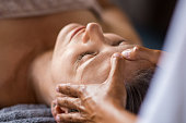 Closeup face of mature woman having facial massage at spa. Senior woman lying with closed eyes at spa while a massage therapist doing anti-aging treatment. Masseur doing head massage at wellness cente