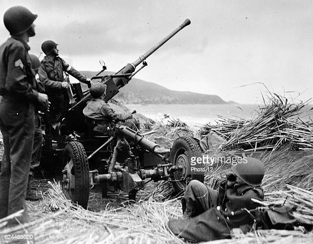 Antiaircraft bofors gun in at position on a mound overlooking the beach in Algeria with a United States antiaircraft artillery crew in position 1943