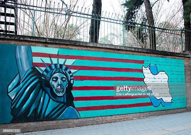 Antiamerican mural propoganda slogan depict statue liberty skeleton on the wall of the former united states embassy central district tehran Iran on...