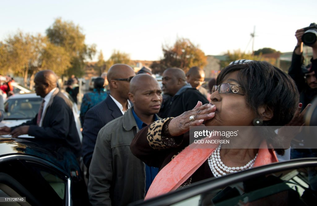 Winnie Madikizela Mandela blows a kiss to well wishers after addressing media outside their first family home in Soweto on June 28, 2013. Winnie Mandela said 'there is great improvement in his health' Mandela is receiving treatment at the Mediclinic heart hospital in Pretoria. Mandela's close family gathered yesterday at his rural homestead to discuss the failing health of the South African anti-apartheid icon who was fighting for his life in hospital. Messages of support poured in from around the world for the Nobel Peace Prize winner, who spent 27 years behind bars for his struggle under white minority rule and went on to become South Africa's first black president. AFP PHOTO / ODD ANDERSEN