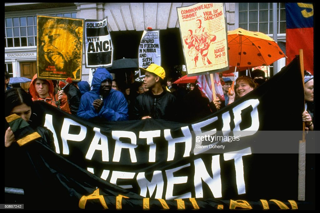 AntiApartheid demonstrators holding vigil for commonwealth decision in favor of economic sanctions toward South Africa w poster of iconic prisoner...