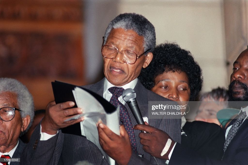 Anti-apartheid leader and African National Congress (ANC) member Nelson Mandela delivers his first public speech in Cape Town, 11 February 1990, since his release from jail. He urged white South Africans to join ANC in working for a new South Africa. At right, Mandela's wife Winnie Mandela.