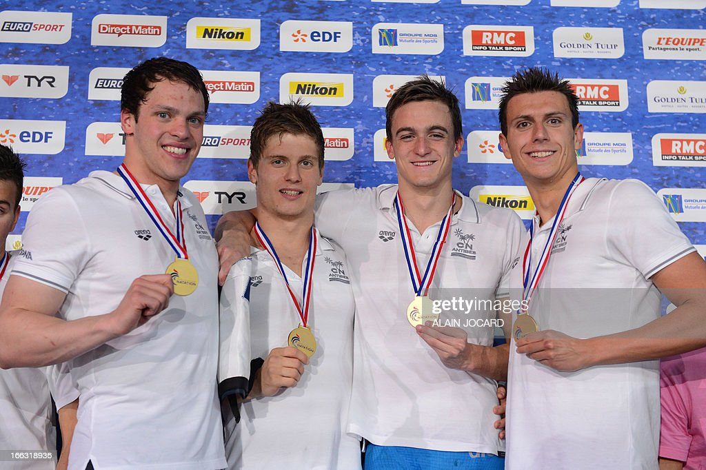 CN Antibes swimming club team Eric Ress, Jean-Baptiste Patamia, Simon Guerin, and Clement Mignon, pose on the podium after winning the 4 X 200 m relay final, on April 11, 2013 during the French swimming championships in Rennes, western France.