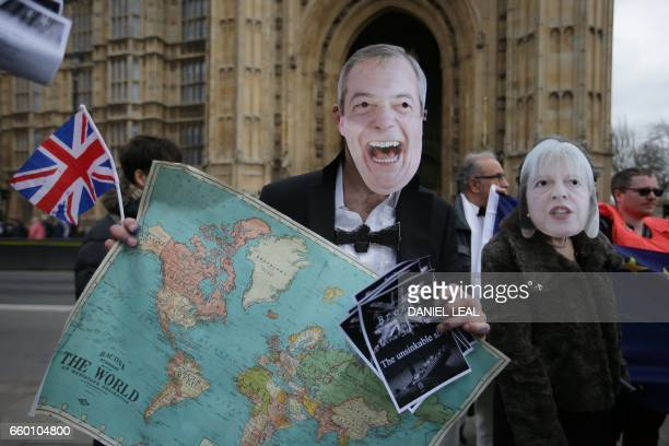AntiBrexit protesters wearing a mask of Nigel Farage former UK Independence Party leader and British Prime Minister Theresa May stand outside the...