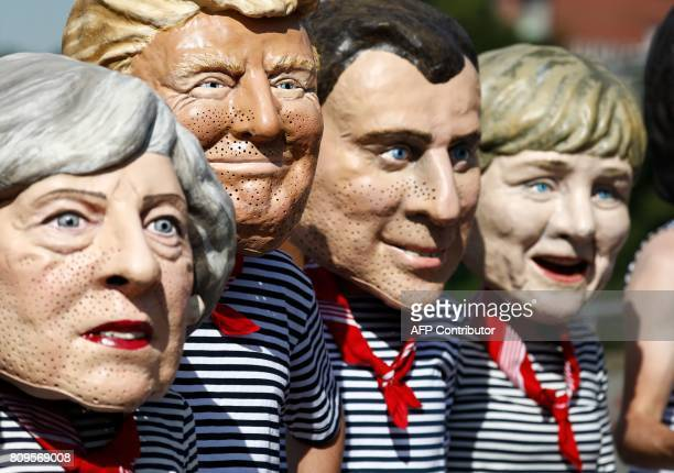 Anticapitalism activists wearing masks of Britain's Prime Minister Theresa May US President Donald Trump French President Emmanuel Macron and German...